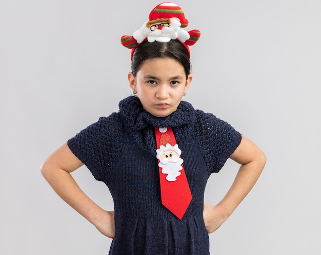 Little girl in knit dress wearing red tie with funny christmas rim on head looking with frowning face with arms at hip