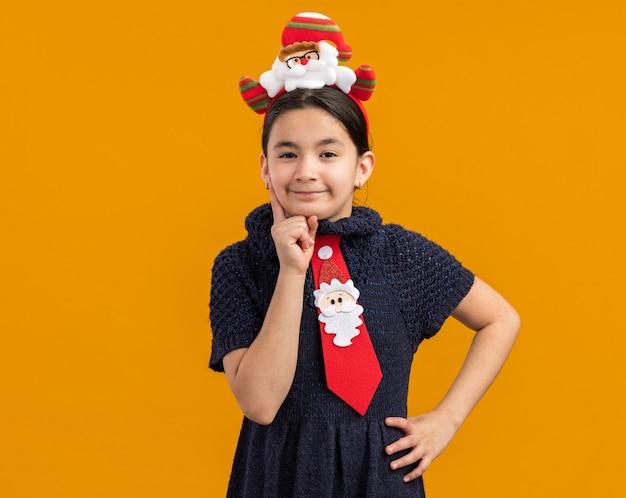 Bambina in abito in maglia che indossa cravatta rossa con bordo divertente di natale sulla testa guardando con espressione scettica
