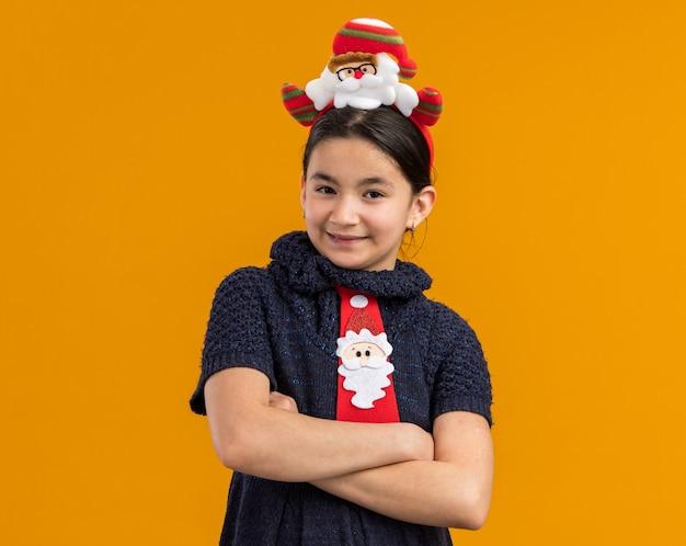 Bambina in abito in maglia che indossa cravatta rossa con bordo divertente di natale sulla testa guardando con il sorriso sul viso con le braccia incrociate