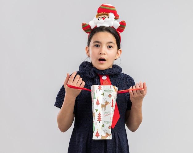 Bambina in abito in maglia che indossa cravatta rossa con bordo divertente di natale sul sacchetto di carta di apertura della testa con il regalo di natale che sembra sorpreso