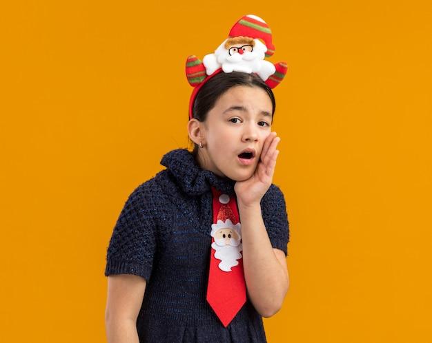Bambina in abito in maglia che indossa cravatta rossa con bordo divertente natale sulla testa che bisbiglia con la mano vicino alla bocca