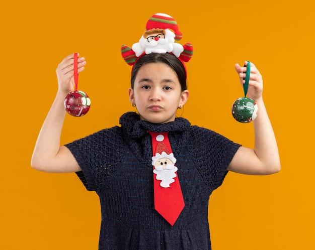 Bambina in abito di maglia che indossa cravatta rossa con bordo divertente sulla testa tenendo le palle di natale guardando la fotocamera con il viso serio in piedi su sfondo arancione