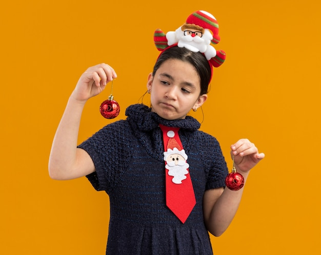 Little girl in knit dress wearing  red tie with funny rim on head holding christmas balls looking confused trying to make choice standing over orange wall