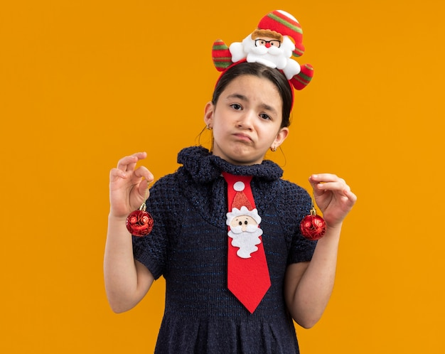Bambina in abito in maglia che indossa cravatta rossa con bordo divertente sulla testa che tiene le palle di natale che sembrano confuse con l'espressione triste
