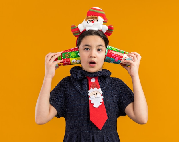 Little girl in knit dress wearing  red tie with funny rim on head holding colorful paper cups over her ears looking surprised    standing over orange wall
