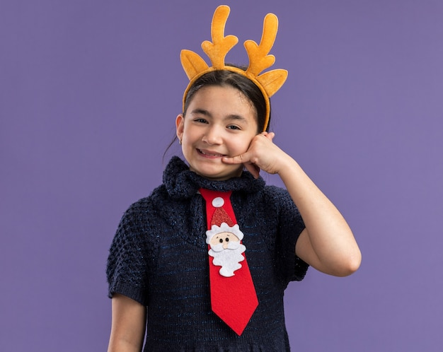 Little girl in knit dress wearing  red tie with funny rim with deer horns on head   happy and positive making call me gesture smiling  standing over purple wall
