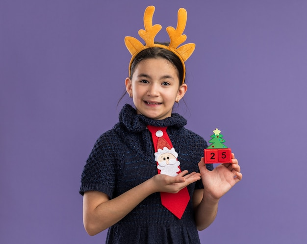 Little girl in knit dress wearing red tie with funny rim with deer horns on head  holding toy cubes with christmas date presenting with arm happy and positive smiling standing over purple wall