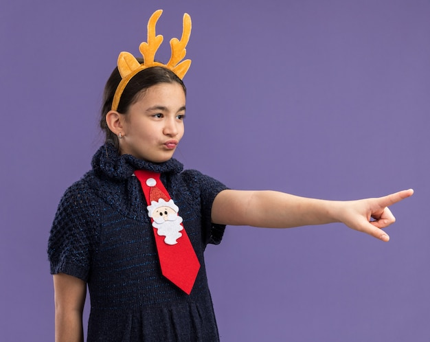 Little girl in knit dress wearing red tie with funny rim with deer horns on head looking aside pointing with index finger at something