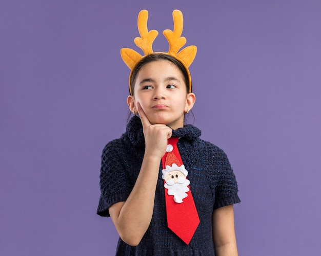Little girl in knit dress wearing red tie with funny rim with deer horns on head looking aside puzzled