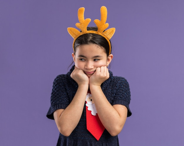 Little girl in knit dress wearing red tie with funny rim with deer horns on head looking aside worried standing over purple background