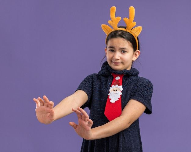 Little girl in knit dress wearing red tie with funny rim with deer horns on head  looking scared making defense gesture with hands  standing over purple wall