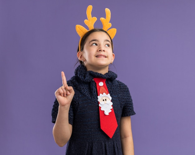 Little girl in knit dress wearing red tie with funny rim with deer horns on head  looking up with smile on surprised face showing index finger having new idea standing over purple wall