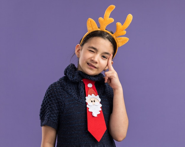 Little girl in knit dress wearing  red tie with funny rim with deer horns on head  pointing with index finger at her head winking   standing over purple wall