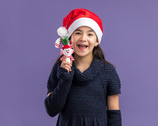 Little girl in knit dress wearing santa hat holding christmas candy cane  happy and cheerful  standing over purple wall