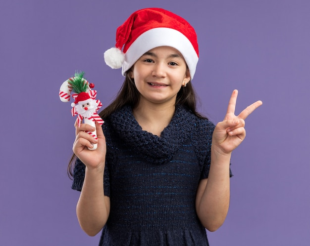 Little girl in knit dress wearing santa hat holding christmas candy cane   happy and positive showing v-sign  standing over purple wall