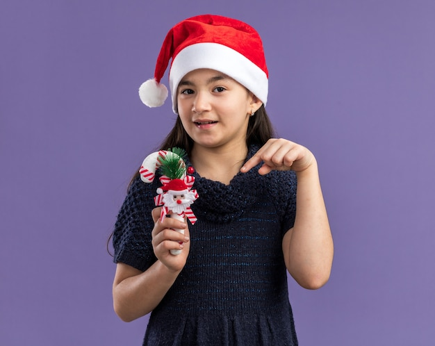 Little girl in knit dress wearing santa hat holding christmas candy cane pointing with index finger at it  with smile on face standing over purple wall