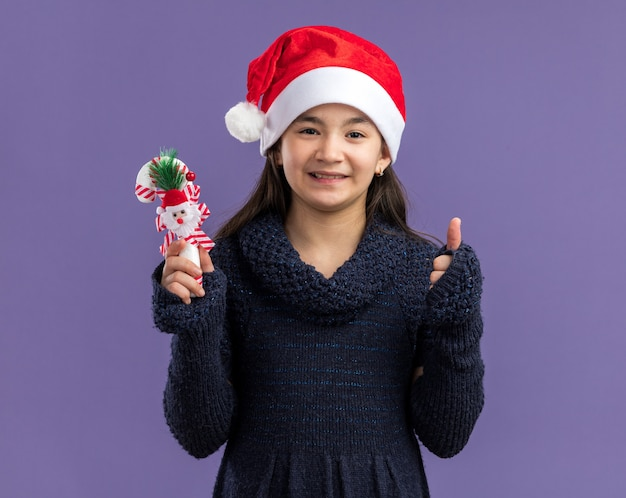 Little girl in knit dress wearing santa hat holding christmas candy cane  smiling cheerfully  standing over purple wall