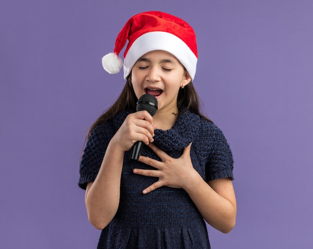 Little girl in knit dress wearing santa hat holding microphone  singing celebrating christmas party  happy and positive standing over purple wall