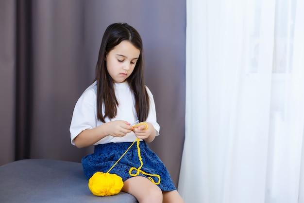 小さな女の子はかぎ針編みを編みます。女の子はソファに座って、編み糸で編みます。太い糸をかぎ針編みします。家の快適さ。