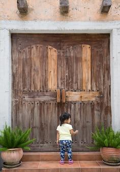 Little girl knocks on the wooden closed door