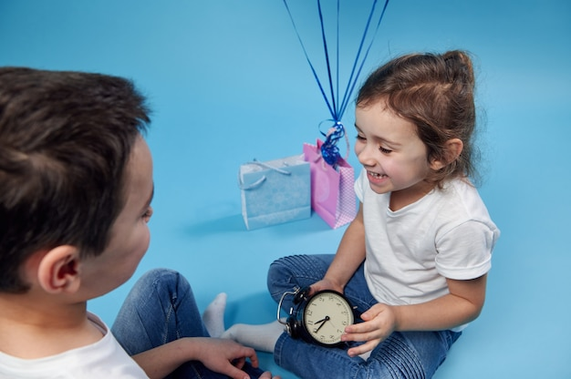 Little girl laughing with an alarm clock in her hands and sitting in a front of a boy on blue surface