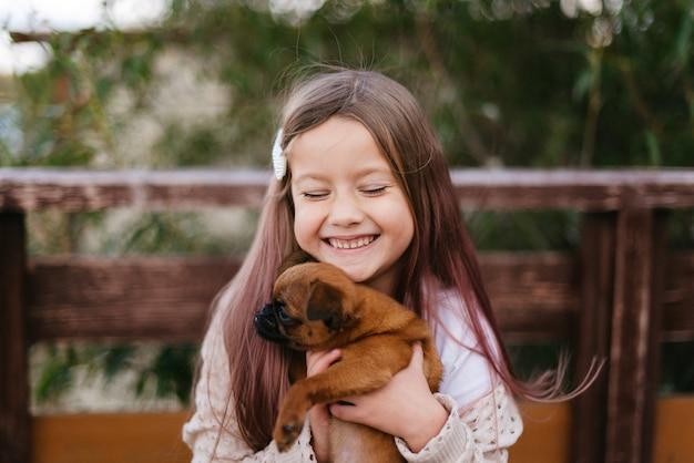 어린 소녀는 웃고 그녀의 팔에 작은 갈색 개를 안고