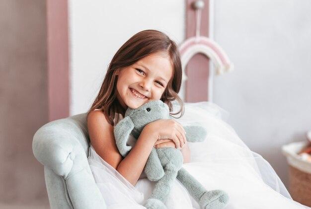 어린 소녀는 어린이 방에서 부드러운 장난감을 가지고 웃고 노는