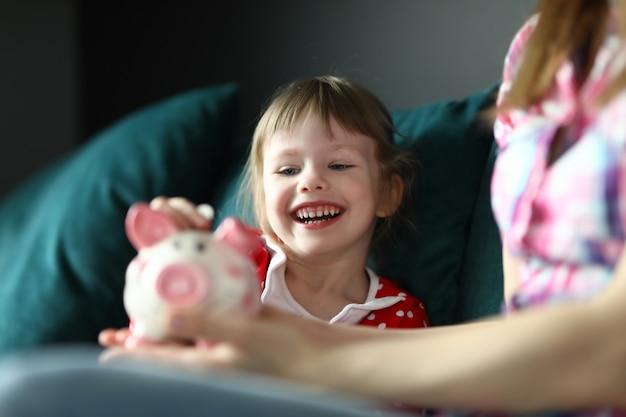 Маленькая девочка смеется и кладет монеты в копилку