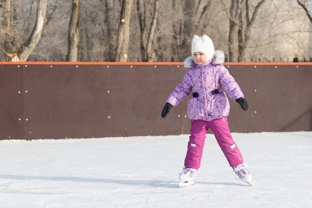 The little girl laughs and skates on the ice.