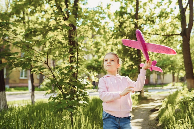 Little girl launches a toy plane into the air in the park