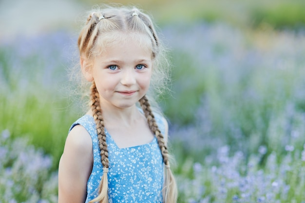 Little girl in lavender field. kids fantasy. smiling girl sniffing flowers in summer purple lavender field.