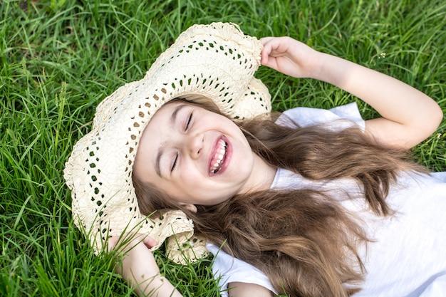 어린 소녀는 잔디에 누워입니다. 여름 시간과 화창한 날