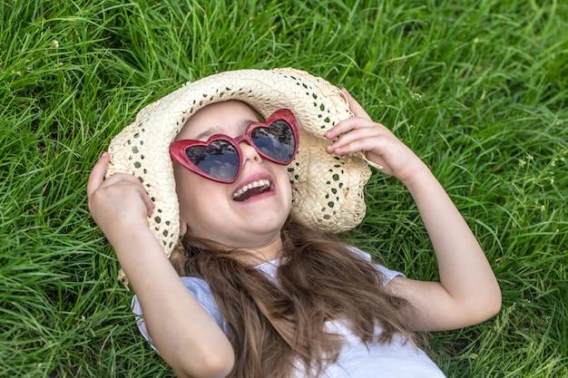 Маленькая девочка лежит в траве летнее время и солнечный день