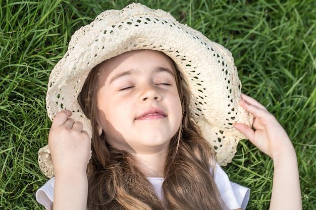 草の中に横たわっている少女。夏時間と晴れた日