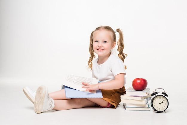 床に横たわって、孤立したノートに絵を描く少女