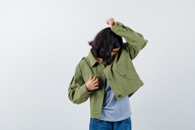 Bambina che si appoggia il viso sulla spalla in cappotto, t-shirt, jeans e guardando malinconico, vista frontale.