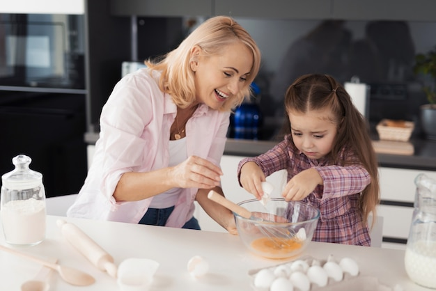 Little girl learn to cook biscuit. her grandmother helps her
