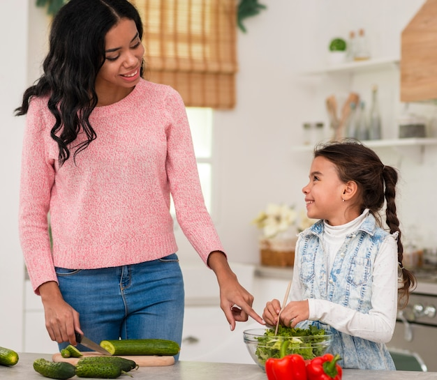 Little girl learning to cook with mom