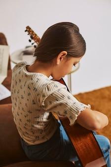 Bambina che impara a suonare la chitarra a casa
