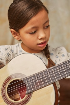 Little girl learning how to play guitar at home