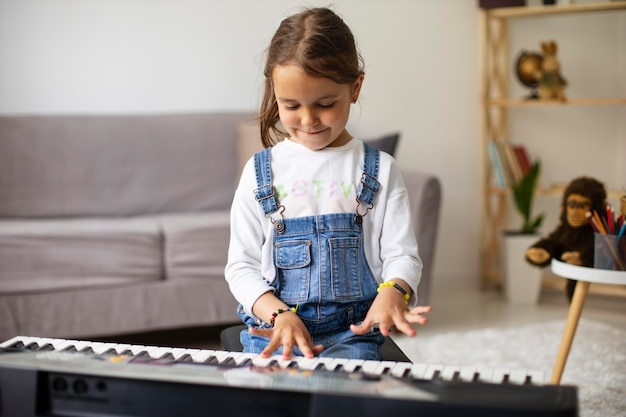 Little girl learning how to play the piano