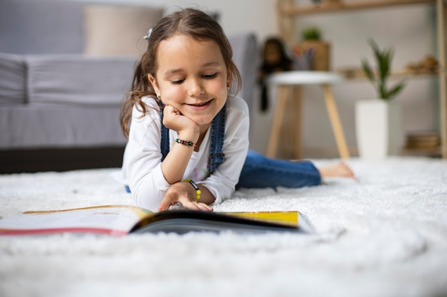 Little girl learning how to read from a book Premium Photo