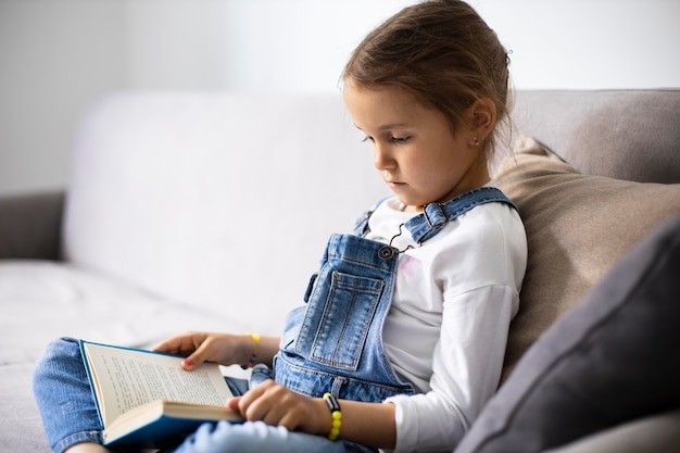 Little girl learning how to read from a book