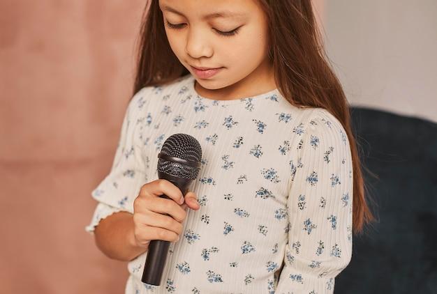 Bambina che impara a cantare a casa con il microfono