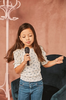 Little girl learning how to sing at home