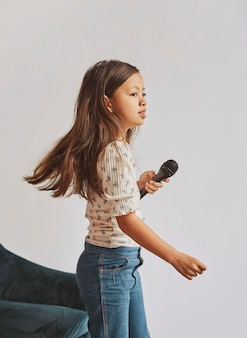 Bambina che impara a cantare a casa