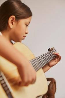 家でギターを弾く方法を学ぶ少女