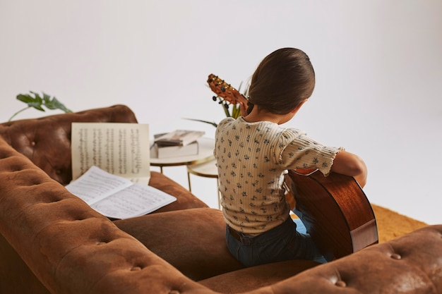 Маленькая девочка учится играть на гитаре дома