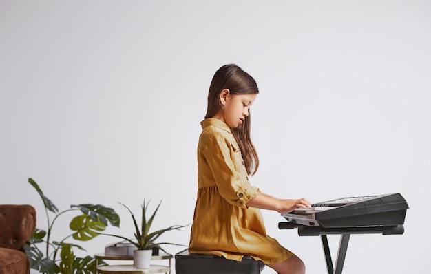 Маленькая девочка учится играть на электронной клавиатуре