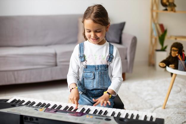 Маленькая девочка учится играть на пианино